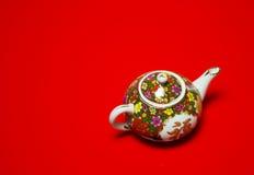 Chinese porseleinkruik voor thee op geïsoleerd rood horizontaal Stock Afbeelding