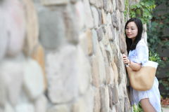 Chinese Portrait of young beautiful woman against to wall in park Stock Image