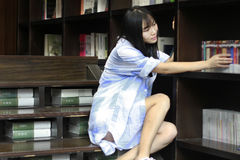 Chinese Portrait of young beautiful woman looking for Book In Bookstore Stock Image
