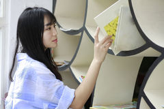 Chinese Portrait of young beautiful woman looking for Book In Bookstore Royalty Free Stock Photo