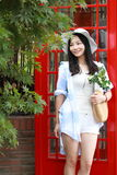 Chinese Portrait of young beautiful woman near the old phone booth Royalty Free Stock Photo