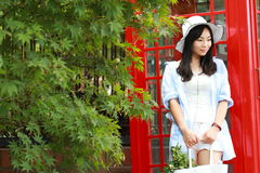 Chinese Portrait of young beautiful woman near the old phone booth Royalty Free Stock Images