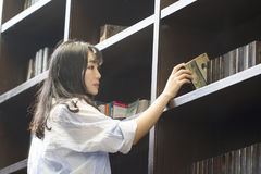 Chinese Portrait of young beautiful woman reaching for a library book In Bookstore Royalty Free Stock Photos