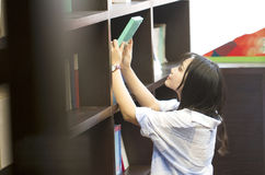 Chinese Portrait of young beautiful woman reaching for a library book In Bookstore Royalty Free Stock Photo
