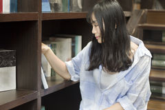 Chinese Portrait of young beautiful woman reaching for a library book In Bookstore Stock Photos