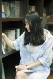 Chinese Portrait of young beautiful woman reaching for a library book In Bookstore Royalty Free Stock Images