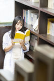 Chinese Portrait of young beautiful woman reads Book In Bookstore Royalty Free Stock Image