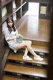 Chinese Portrait of young beautiful woman reads Book In Bookstore Royalty Free Stock Photo