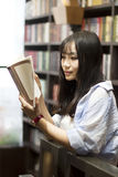 Chinese Portrait of young beautiful woman reads Book In Bookstore Stock Image