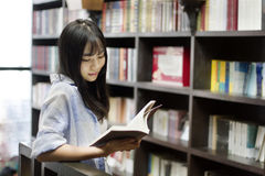Chinese Portrait of young beautiful woman reads Book In Bookstore Royalty Free Stock Photos