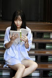 Chinese Portrait of young beautiful woman reads Book In Bookstore Stock Photos