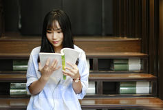 Chinese Portrait of young beautiful woman reads Book In Bookstore Royalty Free Stock Images
