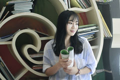 Chinese Portrait of young beautiful woman reads Book In Bookstore Stock Photography