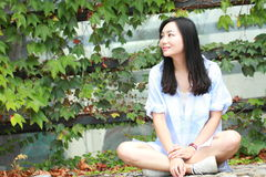 Chinese Portrait of young beautiful woman sit to wall in park Royalty Free Stock Photography