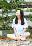 Chinese Portrait of young beautiful woman sit to wall in park Royalty Free Stock Images