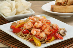 Chinese prawn chow mein. Dish of prawn chow mein with crackers and spring rolls stock photos