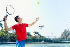 Chinese tennis player ready to hit the ball while serving. Chinese professional tennis player ready to hit the ball with the racket after tossing while serving Royalty Free Stock Photos