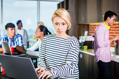 Chinese programmer in lounge of IT start-up. Chinese women programmer in lounge of IT start-up with laptop, co-workers in the background Royalty Free Stock Photography