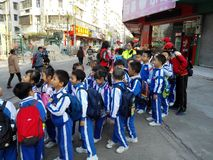 Chinese pupils carry out activities outside school and are on the way. In the morning, a group of pupils carry out activities outside the school and are on the Royalty Free Stock Image