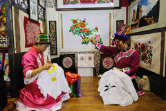 Chinese qiang woman embroidering a picture Royalty Free Stock Photo