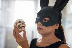 Chinese rabbit mask girl hold skull. Asian Chinese girl with black bunny rabbit mask look and hold small skull on hand with light flare from window. Easter and stock photography