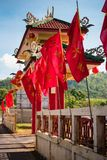 Chinese red flags on blue sky background with big gates. Entrance to the Chinese temple in Phuket with red flags and a large white arch against the blue sky royalty free stock image