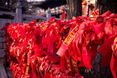 Chinese red ribbons on a fence in Buddhist temple. Royalty Free Stock Photo