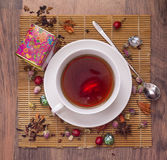 Chinese red Tea  with with rosehip berries. Dried flowers, candied fruit on a bamboo mat. Glass teapot. Painted box with tea. Teaspoon. Wooden background Royalty Free Stock Photos