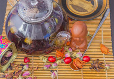 Chinese red Tea  with with rosehip berries. Dried flowers, candied fruit on a bamboo mat. Glass teapot. Painted box with tea. Teaspoon. Wooden background Stock Images