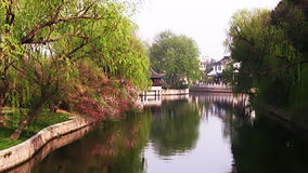 Chinese relaxation. China. Suzhou. A small ripple on the water channel. The water reflected the trees and the traditional Chinese houses stock video footage