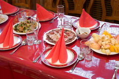 Chinese restaurant banquet table. Chinese restaurant laid table with bright red glossy tablecloth Royalty Free Stock Photos