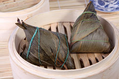 Chinese rice dumplings on bamboo basket. Traditional Chinese rice dumplings (Zongzi or Zong) over bamboo basket. Chinese ZongZi or Zong is traditionally eaten Royalty Free Stock Photos