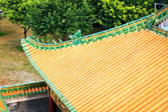 House roof tiles. Asian Chinese traditional house roof of classical building architecture with yellow glazed tiles in Asian ancient style in classic garden in royalty free stock image