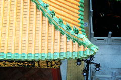 House roof tiles. Asian Chinese traditional house roof of classical building architecture with yellow glazed tiles in Asian ancient style in classic garden in stock photos
