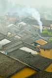 Chinese rooftops in smog. Rooftops and smoke rising from a chimney in a Chinese village Stock Images