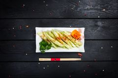 Chinese salad with cucumber and garlic sauce. On white plate, served with chopsticks on wooden background, top view Royalty Free Stock Photo