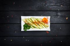 Chinese salad with cucumber and garlic sauce. On white plate, with wooden background, top view Royalty Free Stock Image