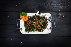 Chinese salad with sea kale with cutlery. Chinese salad with sea kale on the white plate with wooden background, top view Stock Images