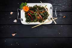 Chinese salad with sea kale served with chopsticks. Chinese salad with sea kale on the white plate served with chopsticks. On black wooden background, top view Royalty Free Stock Image