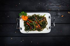 Chinese salad with sea kale. On the white plate on black wooden background, top view Stock Image