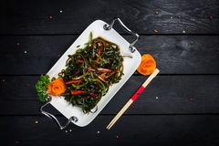 Chinese salad with sea kale with chopsticks. Chinese salad with sea kale on the white plate and black wooden background, top view Stock Images