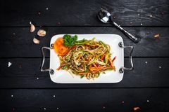 Chinese salad with soy cheese and vegetables. In white plate with cutlery on the wooden background, top view Stock Images