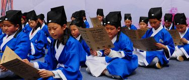 Chinese schoolchild wearing folk clothes studying ancient style prose royalty free stock photo