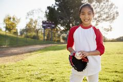 Chinese schoolgirl holding baseball and mitt smiling royalty free stock photo