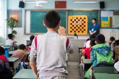Chinese schooljongen die zijn vinger richten op bord Stock Afbeeldingen