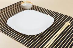 Chinese schotels en eetstokjes op zwarte bamboemat royalty-vrije stock afbeelding
