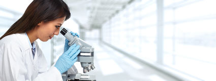 Chinese scientist woman with microscope. Chinese scientist woman working with microscope in laboratory Stock Image