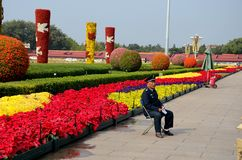 Chinese security guard sits in front of flower display Beijing China. Beijing, China - October 18, 2015: A blue uniformed security guard sits on a chair in front Stock Image