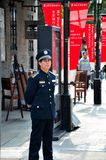 Chinese security guard stands alert Shanghai, China. Shanghai, China - February 16, 2013: A security guard stands and watches in the upmarket Xintiandi stock image