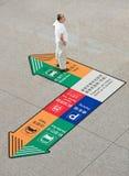 Chinese senior standing on floor signage, Beijing Capital International Airport. Stock Image